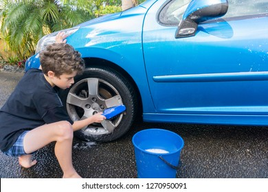 Boy earning pocket money cleaning blue compact car with hose, bucket of water and car brush cleaning wheels.