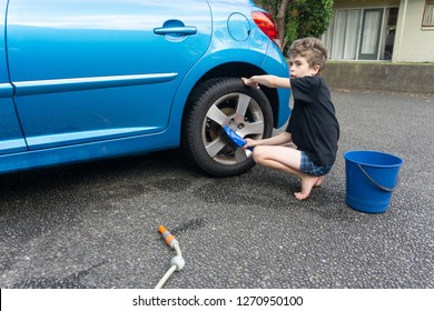 Boy earning pocket money cleaning blue compact car with hose, bucket of water and car brush cleaning alloy wheels