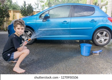 Boy earning pocket money cleaning blue compact car with hose, bucket of water and car brush turns smiles spraying water