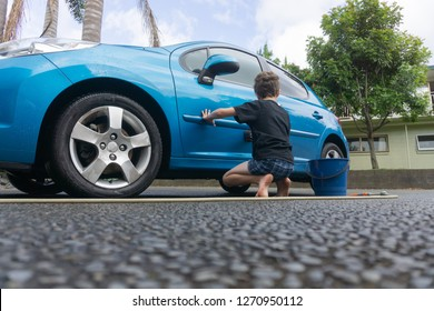 Boy earning pocket money cleaning blue compact car with hose, bucket of water and car brush from low point of view.