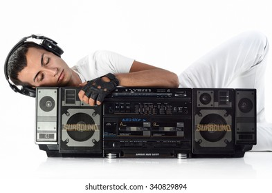 Boy with earphones and ghetto boom box listening music isolated on white background