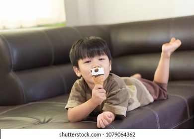 boy eat ice cream,Asian children are playing on sofa,Kid are smiling,People portrait