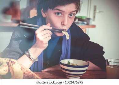 boy is eating asian food with chopsticks