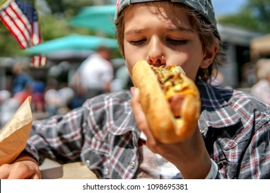 Boy eating barbecue grilled  hot dog on family picnic celebrating independence day with flag on the background, focus on face