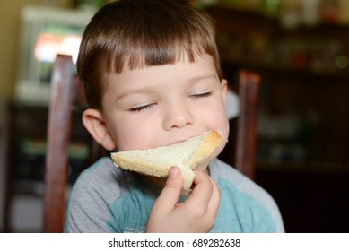Boy eating bread with cream cheese toast. Child eats sandwich with cream cheese for breakfast