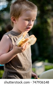 A boy is eating a cheese sandwich outside