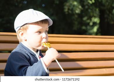 The boy is eating a delicious lollipop.A cute boy licks a lollipop.