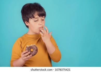 boy eating donut on blue background
