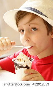 boy eating ice cream with chocolate syrup