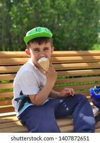 Boy eating ice-cream sitting on bench in park