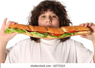 boy eating large sandwich on white background