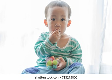 A boy is eating macaroon in the morning.