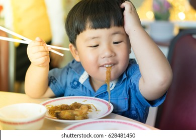 A boy is eating a noodle in a Chinese restaurant.