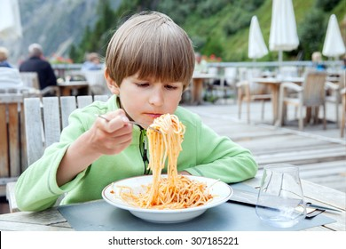 boy eating pasta on the veranda cafe