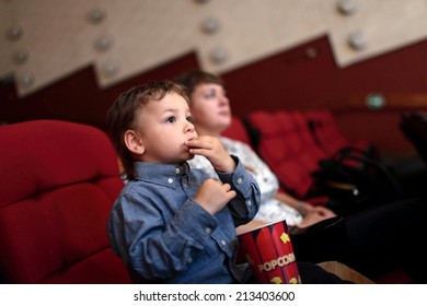 The boy eating popcorn in the cinema