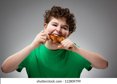 Boy eating roasted chicken leg