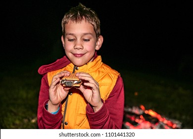 Boy eating smores by the campfire, smiling child enjoys dessert at a summer camp