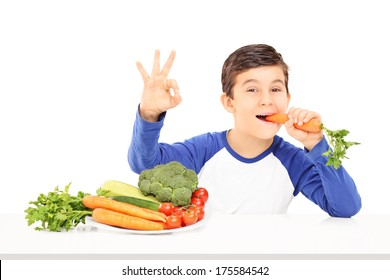 Boy eating vegetables and gesturing happiness with hand seated at table isolated on white background