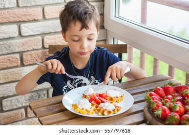 A boy is eating waffles with strawberries and ice-cream over a wooden table on the balcony.
