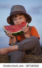 boy eating watermelon on a haystack