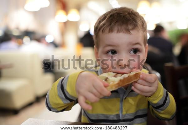 The boy eats bruschetta at a restaurant