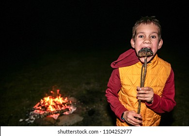boy eats burnt marshmallow by the campfire. child eating smores. Copy space for your text