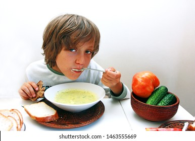 boy eats vegetable soup with spoon and bread at the dinner table