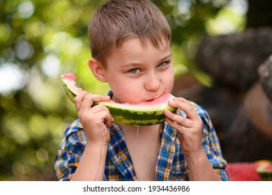 A boy eats a watermelon. Close-up portrait. Delicious and healthy. The rind of the watermelon core remained.