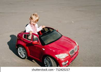 The boy in an embroidered shirt rides on a red, gorgeous car on the road. Close up. Little baby boy. The baby is driving the car.