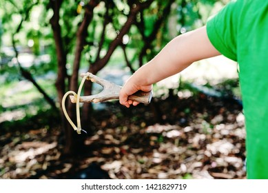 Boy enjoying his summer vacation throwing rocks with a slingshot in a forest.