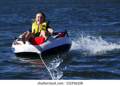 Boy Enjoying Skiing on Inflatable Behind Speed Boat
