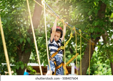 Boy enjoys climbing in the ropes course adventure.