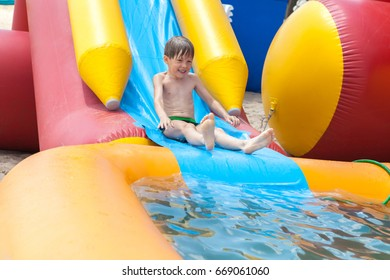 The boy is entertained outdoors, bathed in an inflatable pool. Slides down from the slide into the water.