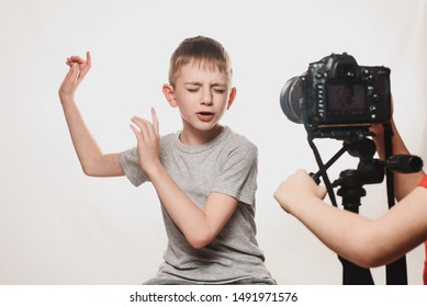 Boy enthusiastically sings in front of the camera. Children's hands with a camera in the frame. Young video blogger. White background