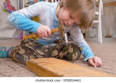The boy is a European, five years old. The child learns to hammer in nails. Real people in the photo.