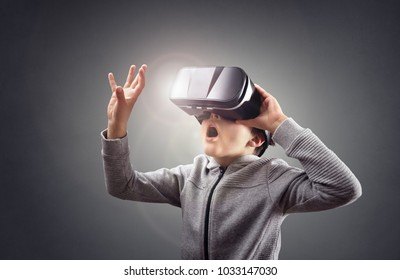Boy experiencing using a virtual reality headset trying to touch something