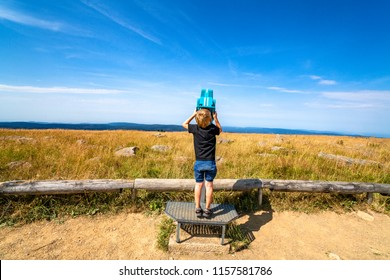 Boy exploring the sky and looking through binoculars on a mountain