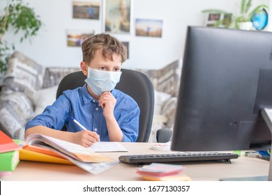 Boy in face mask with computer does his homework during a coronavirus quarantine. concept of online education. Social distance, self- isolation. Distance learning due to virus, flu, epidemic COVID-19