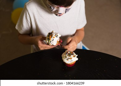 Boy with a face paint eating spooky Halloween cupcakes