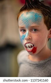 Boy with face painted like a shark