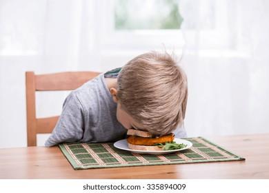 Boy falling asleep and landing face in food