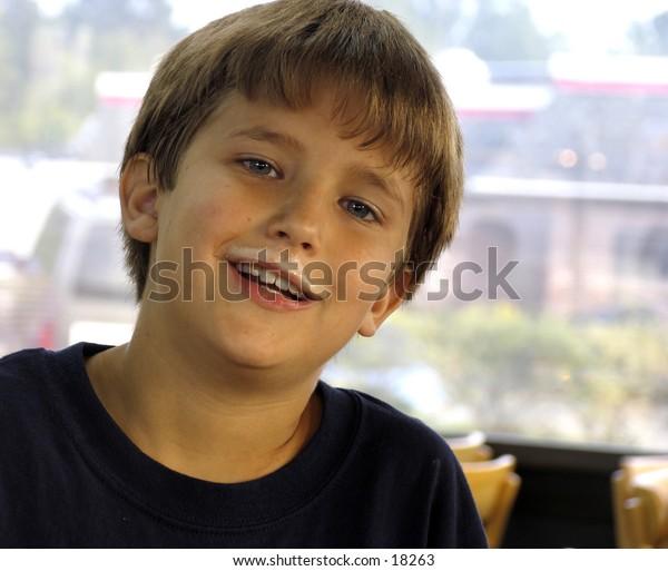 boy in a fast food restaurant with milkshake mustache on his upper lip