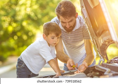 The boy and the father check the oil level in the car