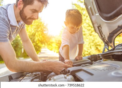 The boy and the father fixing a car