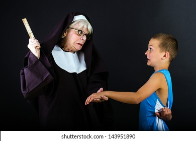 A boy with a fearful expression as a nun is about to hit him with a ruler