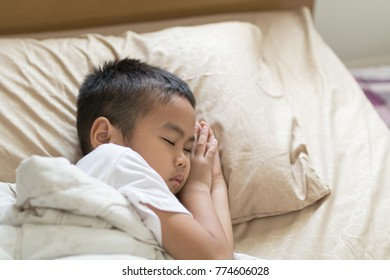 The boy is feverish and is sleeping in bed