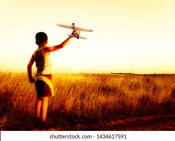 Boy in the field launches a plane