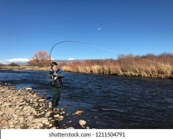 Boy fighting a big fish with a fly rod in a mountain river