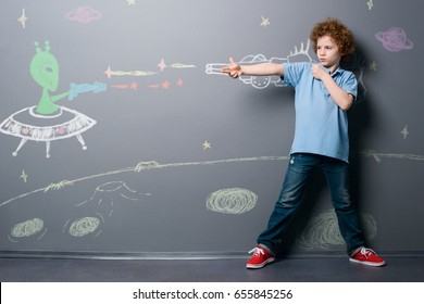 Boy fights with alien soldier. Child shoots at the enemy with laser gun while he is on moon surface under the starry sky, depicted with chalk.
