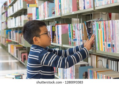 A boy finding a book in the bookshelf at the library